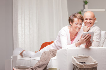 mature couple watching funny things on a tablet