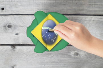 Brazil saving concept with little hand dropping a coin into pigg