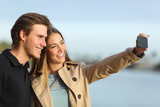Happy couple photographing a selfie with the smart phone