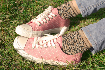 Feet in sneakers on grass background
