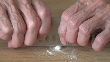 Elder woman cutting pills in exact doses