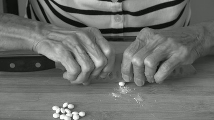 Elderly woman cutting pills in exact doses