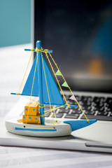 Ship toy on the laptop, travel concept.