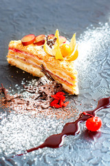 Piece of delicious layered cake with whipper cream on black back