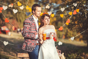 Newlyweds standing embracing in autumn park