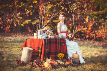 Bride sitting near the table in autumn forest