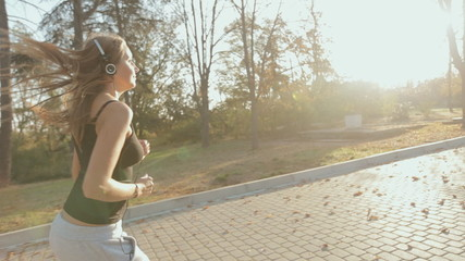 Slim girl runing through the park and listening to music player
