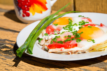 eggs, green onions and tomatoes on an old wooden table