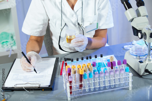 A woman holding a urine sample in his hand - 72704102