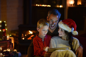 lovely family sharing a digital tablet near the wood stove on a