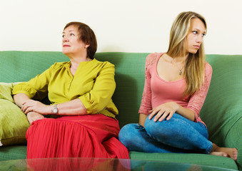 Sad young woman and  mature mother after conflict