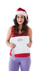 Festive fit brunette holding page and measuring tape