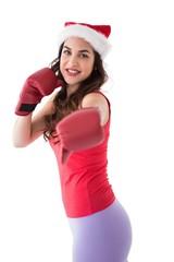 Festive brunette in boxing gloves punching