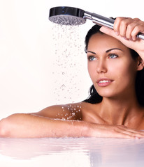 woman holds shower in hands  with falling water