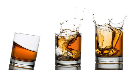 Whiskey glasses with splash, isolated on white
