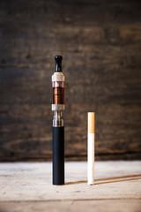 E-Zigarette und Zigarette vor Hintergrund aus Holz