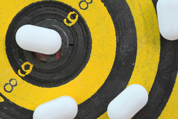 White pills on yellow and black dart target