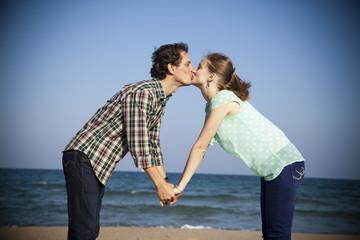 Pareja de novios dándose un beso en la playa
