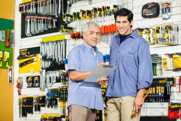 Father And Son With Clipboard In Hardware Store