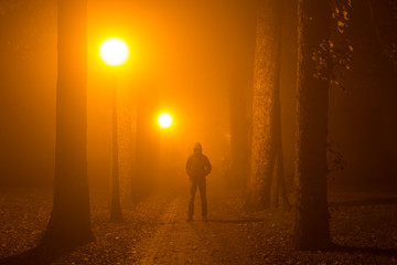 Man alone standing in the middle of a lane on a foggy night.