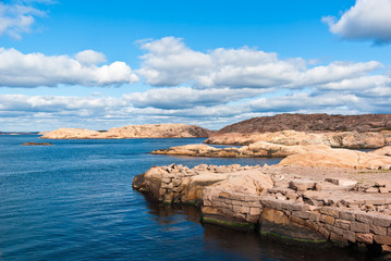 Seascape with red granite boulders and ocean.
