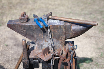 old anvil with many blacksmith tools