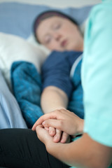 Holding the patient's hand