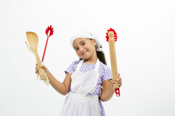 Adorable little girl chef with kitchen utensils and cap
