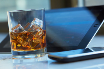 whiskey with ice, the tablet and phone on the table
