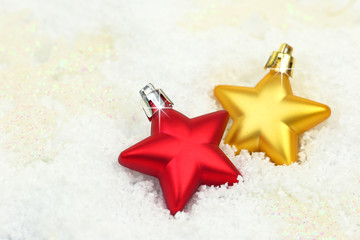 Two Christmas ornaments in shape of star on snow