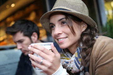 Woman with hat sitting at coffee shop holding hot drink cup
