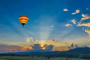 Hot air balloon over the fields at sunset