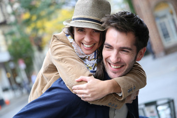 Man giving piggyback ride to girlfriend, having fun