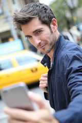 Guy making selfy with smartphone in street of New York
