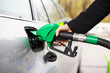 canvas print picture - Hand holding fuel pump and refilling car at petrol station