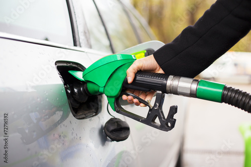 Hand holding fuel pump and refilling car at petrol station - 72716592