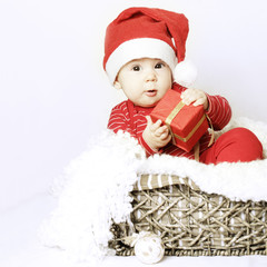 New Year baby wear santa hat and Xmas gift in her hand