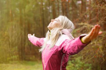 Woman breathes fresh air outdoors in autumn