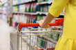 Woman with shopping cart in supermarket - 72719182