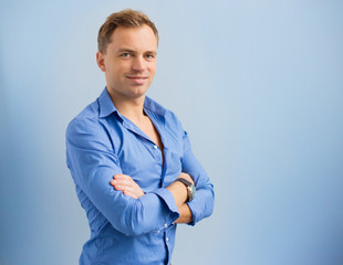 Young man with arms crossed against blue background