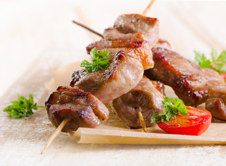 Pork kebabs served with vegetables on wooden table