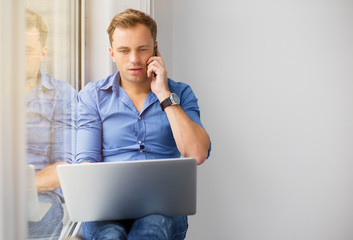 Busy man working with computer while talking on phone