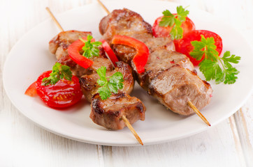 Pork kebabs served with vegetables on  white plate