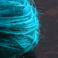 Close-up view of a roll of string on a brown rustic background