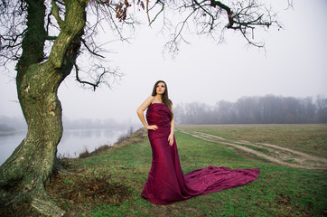 A girl in a long red dress on the River