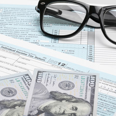 US Tax Form 1040 with glasses and 100 US dollars