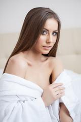 Portrait of sexy brunette posing in bathrobe