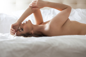 Side view of nude sensual woman in bed