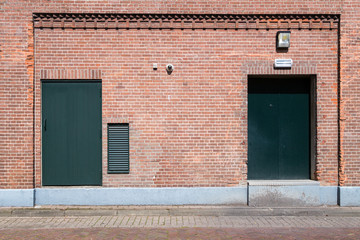 Old brick wall with doors and street