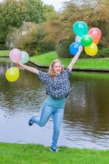 Girl holding up many coloured balloons at pond